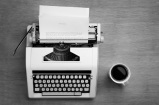 Typewriter with bible script on the paper and a mug of coffee